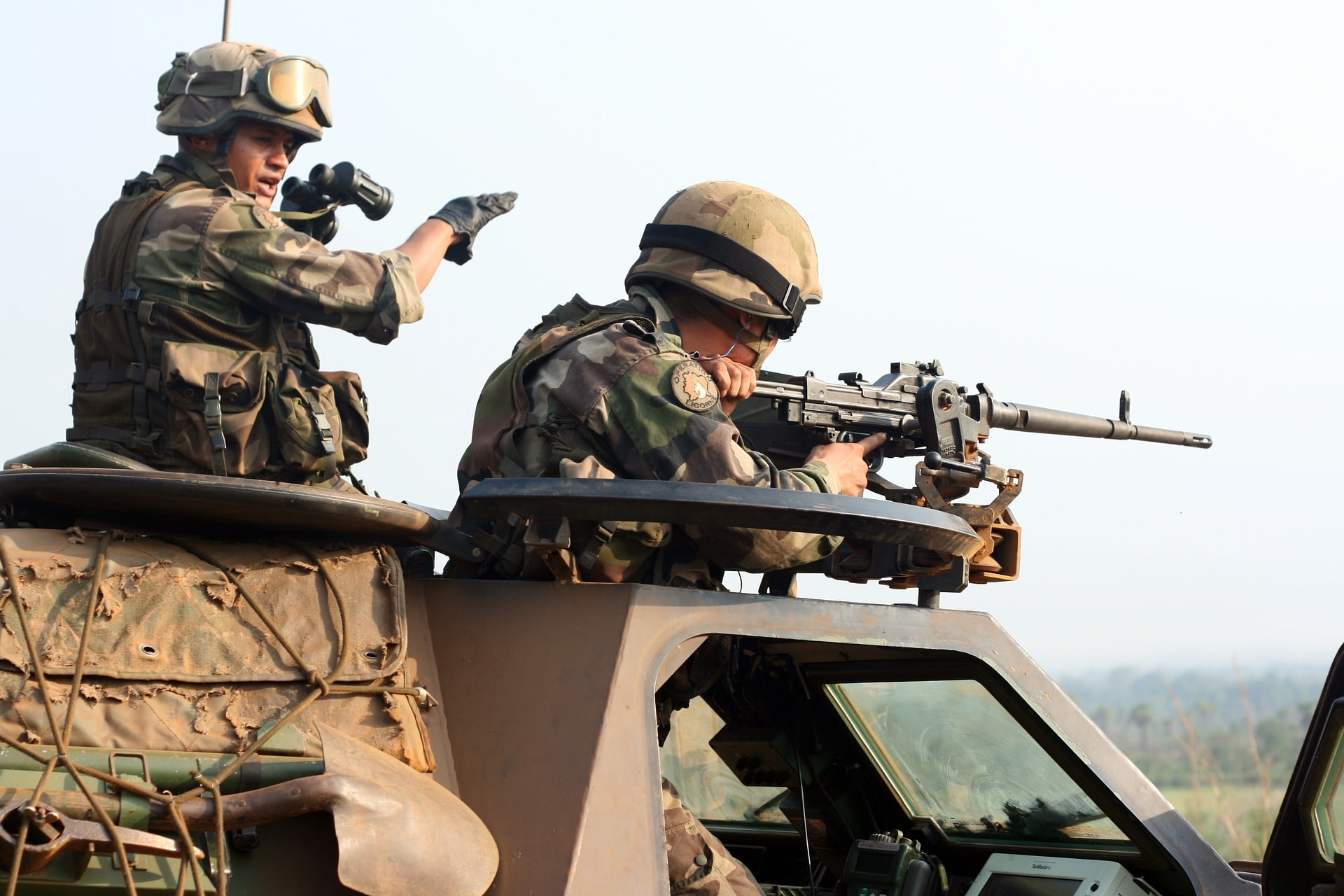 two soliders with weapons on an armored truck