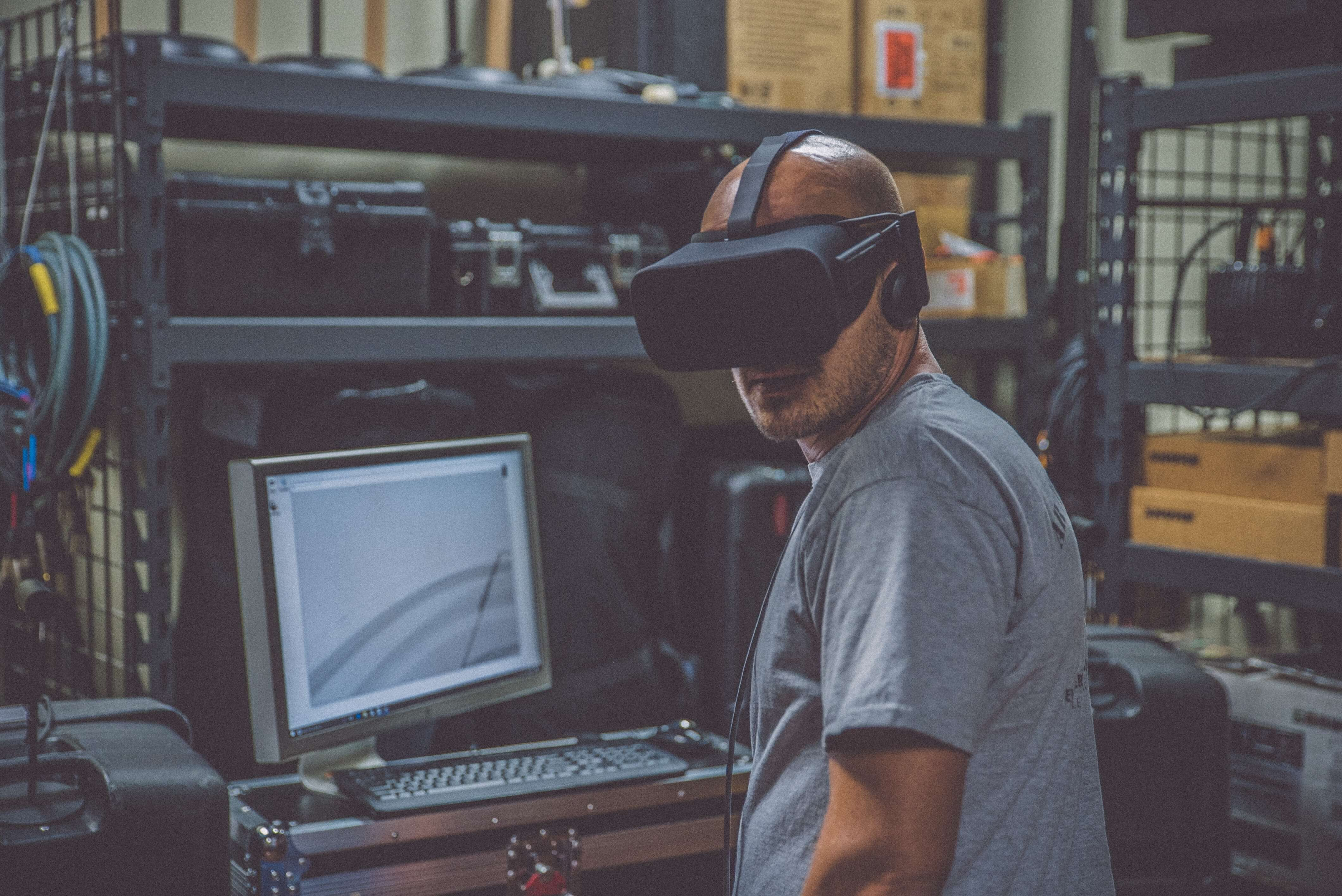 man in VR headset standing in front of a computer